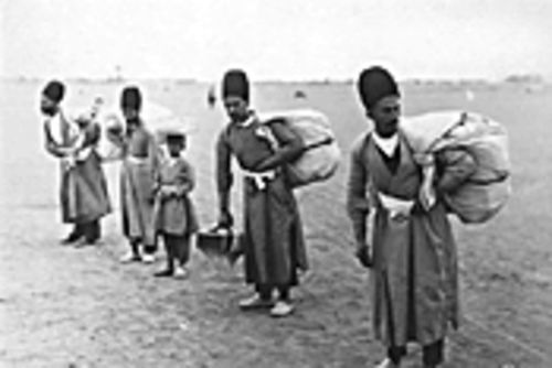 Luggage bearers stand ready in this Sevruguin photo, circa 1890