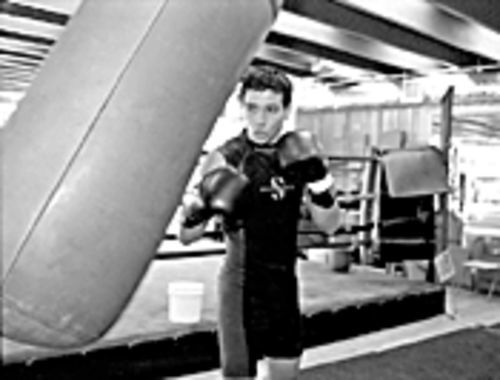 Sergio Garcia, age 21, sweats in a wet suit at Warrior's Gym in Hollywood, hoping to follow in the footsteps of his sparring partner, Daniel Santos.