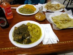 A feast at the Curry Hut in Margate includes chicken curry with potato, pumpkin and chickpeas/potato, dhalpourie roti stuffed with lentil flour, hot peppa sauce, and a cold Dragon Stout and Solo orange.