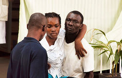 Natanael Louissant, 15, is helped into Bernard Mevs by her father. Doctors believe she contracted hemorrhagic dengue fever.