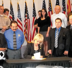 Arizona Gov. Jan Brewer signs Senate Bill 1070.
