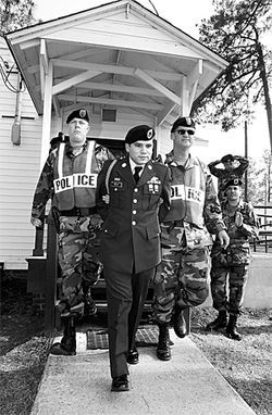 From left: On May 21, 2004, two military police officers led Camilo away in handcuffs following his conviction on desertion charges.