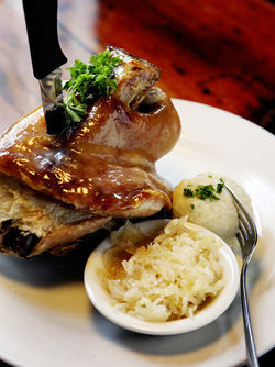 Enjoy the roast pork shank with potato dumpling and sauerkraut at Old Heidelberg.