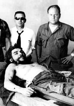 Gustavo (right) stands over the lifeless body of Che Guevara.