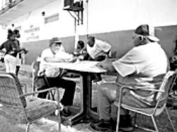 A.B. Burch and Ray Golden's father, Jackie, study their domino moves on the side of Bobby's Market in southwest Belle Glade.