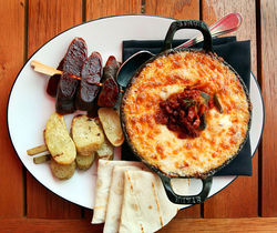 Cazuela De Queso Fundido: served with grilled chorizo and fingerling potatoes on the side.