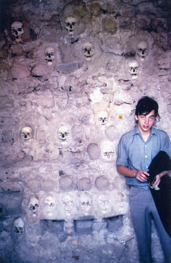 A teenaged Mickey poses next to a wall of skulls during a trip behind the Iron Curtain.