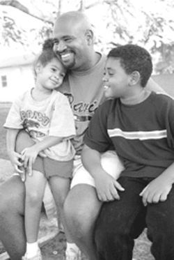 Three-year-old Sarah and nine-year-old Lorenzo dote  on their dad, Richard Sr., in a quiet moment at Potter  Park