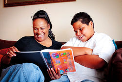 Khalilah reads to Gianni Martinez from her children&#039;s coloring book, Old Fashioned Values and Good Manners, Coloring to Learn.