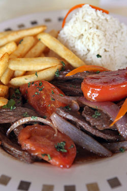 Lomo saltado: Sautéed beef strips, with fresh tomatoes, onions, and French fries.