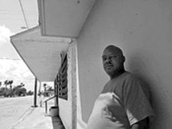 Robert Love stands beside the street where he was beaten by Pahokee police this winter, the climax of a yearlong feud.