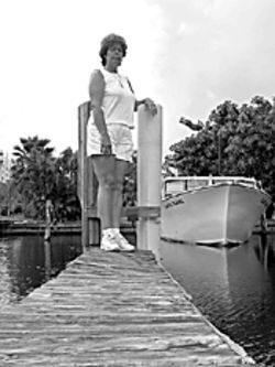 Teri Nielsen stands on a dock at Milt's Marina in Dania Beach. Behind her is the 51-foot Lady Mary.