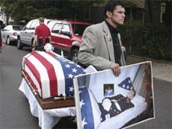 Carlos walks in a parade with a coffin representing his dead son.