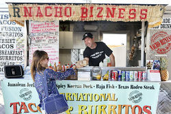 Regular customer Anais Levert receives her lunch order from Aaron Byers of Nacho Bizness.