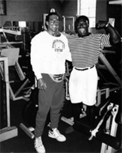 Gil Fernandez Jr. poses in his gym with eight-time Mr. Olympia Lee Haney.
