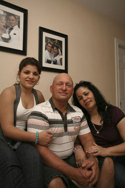 Nelson Diaz poses with his wife, Maritza, and his daughter Islen. Diaz (bottom), who once umpired Olympians and Major Leaguers, now works no-level youth games around Miami.