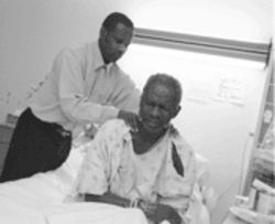 Jean Hyppolite, who is fighting for his life, is comforted in the hospital by his old friend