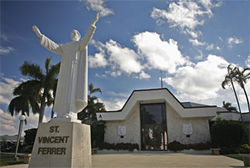A statue of St. Vincent Ferrer welcomes worshipers in front of the church sanctuary on a sun-drenched day.