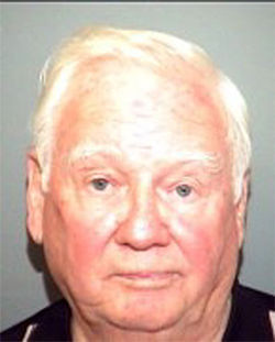 Father John Skehan poses for a police mug shot.