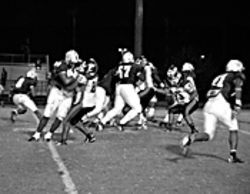 Randy Phillips (number 8, left), in at running back against Forest Hill, makes a cut. The Raiders go on to win 58-0.
