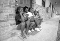 Francine Mathis sits outside her Dania Beach apartment, flanked by her two 13-year-old daughters, Shaquanda Peterson (left) and Ayanna Smith. Daughter Angel Lee, age 4, sits on her lap.
