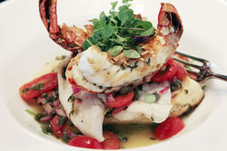 South African lobster tail and fillet of basso with white wine broth, tomatoes, and capers.