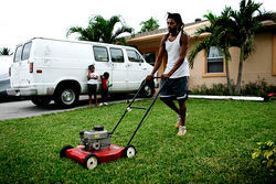 Fabian Ferguson mows the lawn at his adversely possessed home on a quiet street in North Lauderdale.