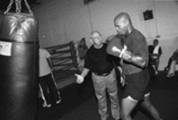 Trainer Angelo Dundee uses an instructive right hand to sharpen cruiserweight Kenny Lunkins