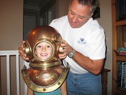 Lahey puts an old-fashioned diving helmet on his daughter, Victoria.