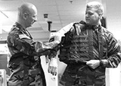 Army Col. Ed Donnelly shows off the Interceptor body armor worn by Maj. David Delmonte.